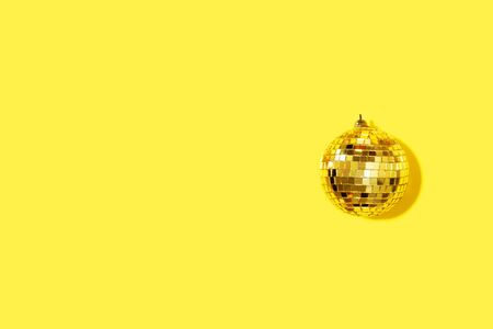 Gold mirror disco ball on yellow background. Flat lay, top view. Minimal New year party concept. Christmas greeting card with copy space. Stock Photo