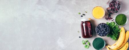 Banner of ingredients for heavy metals detox smoothie. Bilberry, barley grass, spirulina, orange juice, dulse and cilantro on gray background. Top view. Healthy eating, alkaline diet, vegan concept