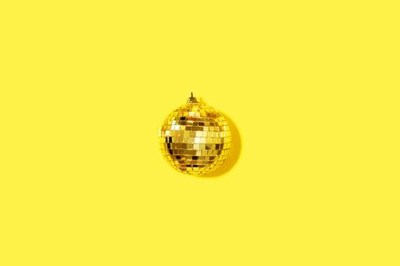Creative Christmas composition. Flat lay, top view. Disco ball bauble on yellow background with copy space. Minimal New year party concept. Minimal Christmas gold decoration. Stock Photo