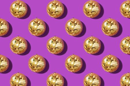 Christmas gold baubles organized on violet background. Top view. Flat lay. Creative New year pattern. Party time concept. Banner.