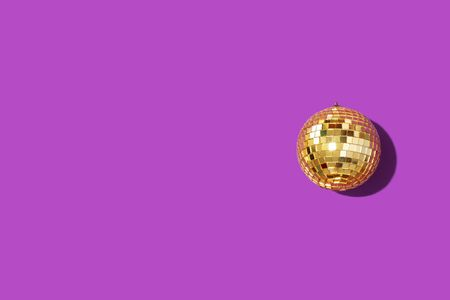 Gold mirror disco ball on violet background. Flat lay, top view. Minimal New year party concept. Christmas greeting card with copy space.