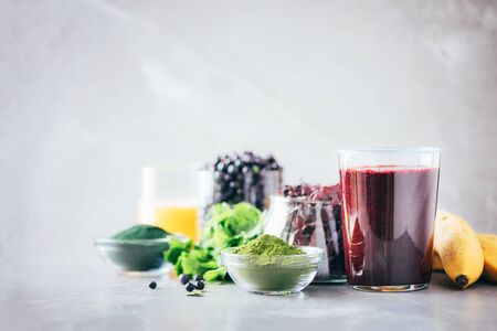 Healthy eating, alkaline diet, vegan concept. Blueberries, bilberry, barley grass juice, spirulina, orange juice, dulse and cilantro on marble background. Ingredients for heavy metals detox smoothie 写真素材 - 129996318
