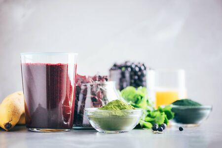 Healthy eating, alkaline diet, vegan concept. Blueberries, bilberry, barley grass juice, spirulina, orange juice, dulse and cilantro on marble background. Ingredients for heavy metals detox smoothie