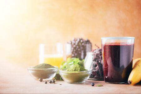 Healthy eating, alkaline diet, vegan concept. Blueberries, bilberry, barley grass, spirulina powder, orange juice, dulse, cilantro on marble background. Ingredients for heavy metals detox smoothie