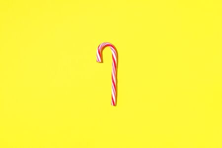 Christmas candy cane on yellow background with copy space. Top view. Greeting card on Christmas and New Year. Minimal festive concept.