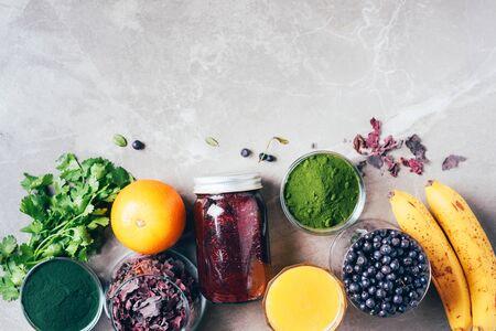 Blueberries, bilberry, barley grass, spirulina, orange juice, dulse, cilantro on marble background. Top view. Healthy eating, alkaline diet, vegan concept. Ingredients of heavy metals detox smoothie 写真素材 - 129996323
