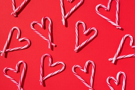Pattern with hearts made of Christmas candy canes on red background. Top view. Flat lay. Love, Valentines day concept. New year and Christmas card. Stock Photo