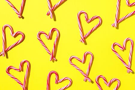 Pattern with hearts made of Christmas candy canes on yellow background. Top view. Flat lay. Love, Valentines day concept. New year and Christmas card. Stock Photo