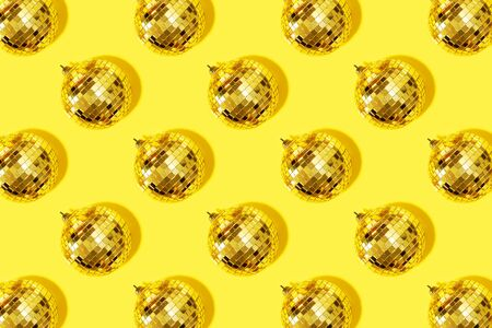 Creative Christmas pattern. Shiny gold disco balls over yellow background. Flat lay, top view. New year baubles, star sparkles. Party time. Cristmas greeting card.