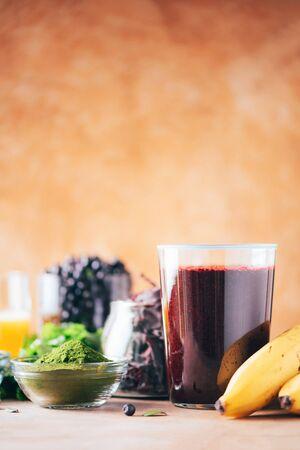 Fresh blueberries, bilberry, barley grass, spirulina powder, orange juice, dulse, cilantro on marble background. Heavy metals detox smoothie. Healthy eating, alkaline diet, vegan concept 写真素材 - 129996331