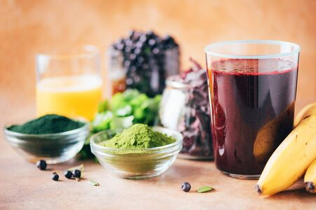 Heavy metals detox smoothie. Blueberries, bilberry, barley grass juice extract, spirulina powder, orange juice, dulse and cilantro on marble background. Healthy eating, alkaline diet, vegan concept. 写真素材