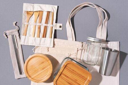 Baumwolltaschen, Glas, Flasche, Metallbecher, Trinkhalme, Bambusbesteck und Kisten auf grauem Hintergrund. Nachhaltiger Lebensstil. Zero Waste, plastikfreies Einkaufskonzept