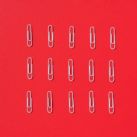 White paper clips on pastel red background. Top view, flat lay. Back to school concept. College, institute education, office work. Фото со стока