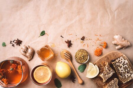 Ingredients for healthy hot drink. Lemon, calendula, ginger, mint, honey, apple and spices over craft paper background. Copy space. Top view. Alternative medicine concept. Clean eating, detox.