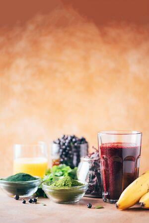 Heavy metals detox smoothie. Blueberries, bilberry, barley grass juice extract, spirulina powder, orange juice, dulse and cilantro on marble background. Healthy eating, alkaline diet, vegan concept Banque d'images