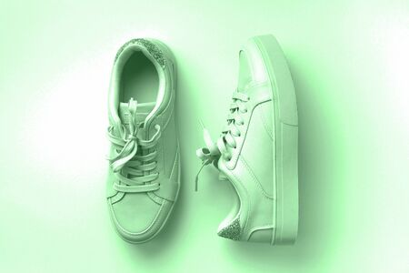 White leather sneakers on mint background. Pair of fashion trendy white sport shoes or sneakers with copy space for text or design. Overhead shot of new white sneakers,monochrome. Top view or flat lay.