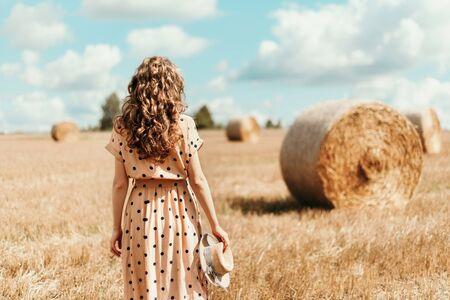 Young woman standing on harvested field with straw bales. Agriculture background with copy space. Summer and autumn harvest concept. Thanksgiving day.