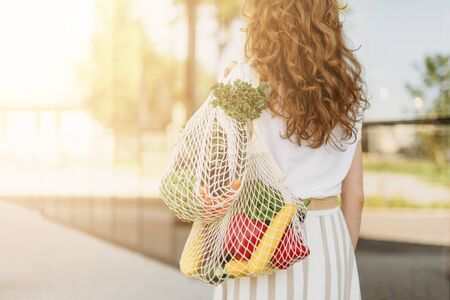 Zero waste concept with copy space. Woman holding cotton shopper and reusable mesh shopping bags with vegetables, products. Eco friendly mesh shopper. Zero waste, plastic free concept Banco de Imagens