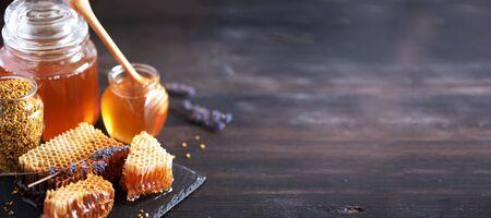 Bee pollen granules, honey jar with wooden dropper, honeycomb on dark backdrop. Copy space. Autumn harvest concept.