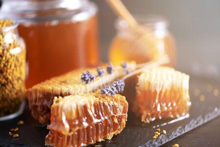 Fresh honeycombs pieces, dry lavender flowers on black background. Autumn harvest concept. 版權商用圖片