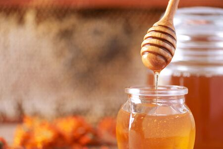 Honey dripping from wooden honey spoon in jar on grey background. Copy space. Autumn harvest concept Banner.