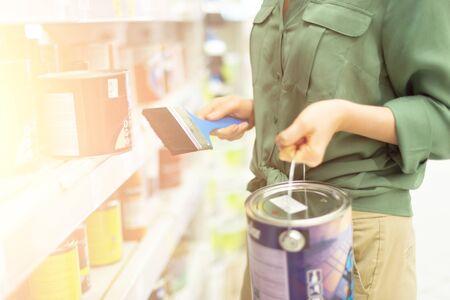 金物店で買い物をする女性。女の子は、塗料店で塗料を選択しています。コピースペースのあるバナー。