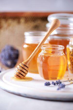 Herbal honey with lavender flowers, bee pollen granules, honey conb on grey background. Autumn harvest concept. 版權商用圖片