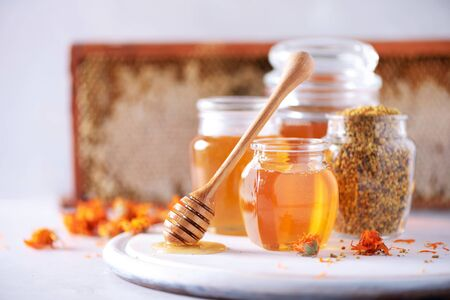 Miel de hierbas en tarro con cucharón, panal, gránulos de polen de abeja, flores de caléndula sobre fondo gris