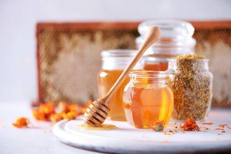 Miele di erbe in barattolo con mestolo, favo, granuli di polline d'api, fiori di calendula su sfondo grigio