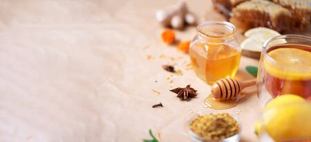 Ingredients for healthy hot drink. Lemon, ginger, mint, honey, apple and spices on craft paper background. Copy space. Alternative medicine concept. Clean eating, detox. Banner.