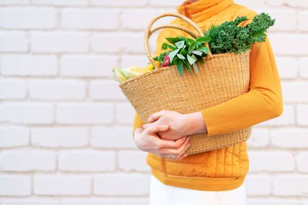 Woman hand holding straw basket with organic vegetables over brick background. Healthy food, vegetarian diet. Eco friendly, zero waste, plastic free concept Stock fotó