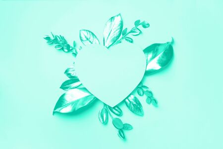 Golden leaves, heart shaped paper on mint background with copy space. Top view. Trendy green and turquoise color. Creative design elements for invitation, wedding cards, valentines day.