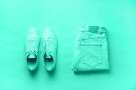 Female white sneakers and jeans, striped t-shirt on mint color background with copy space. Top view. Summer fashion, capsule wardrobe concept. Biscay Green color of the year 2020 Reklamní fotografie