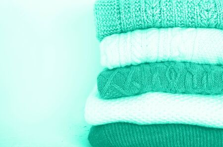 Pile of knitted wool sweaters in mint color background with copy space. Knitwear, clothes. Trendy green and turquoise color Reklamní fotografie