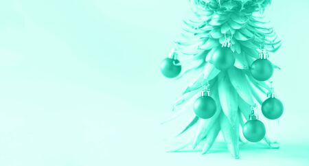 Creative Christmas tree made of pineapple and baubles on mint color background, copy space. Greeting card, decoration for new year party. Trendy green and turquoise color. Banner. Zdjęcie Seryjne