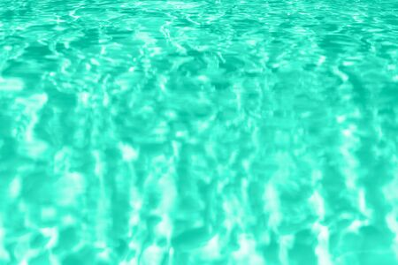 Close up abstract water texture. Swimming pool water in mint color background. Trendy green and turquoise color. Copy space, top view