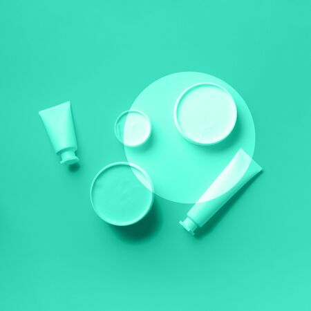 Cosmetics, skin care, beauty, body treatment concept. White cosmetic jar, tube, bottle and tropical monstera leaf over mint color background. Trendy green and turquoise color