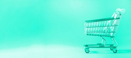 Shopping cart on mint color background. Minimalism style. Creative design. Copy space. Shop trolley at supermarket. Sale, discount, shopaholism concept. Trendy green and turquoise color Reklamní fotografie