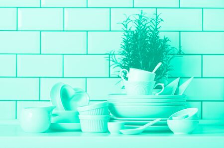 White tableware for serving. Dishes, cups, spoons, utensils and other different white stuff on table-top. Kitchen accessories. Trendy green and turquoise color. Minimal and clean concept.