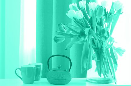 Bouquet of beautiful tulips in vase, cup, saucer and teapot on mint color. Trendy green and turquoise color. Free space for your text