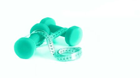 Fitness concept. Dumbbells and measuring tape in mint color background. Trendy green and turquoise color. Copyspace.