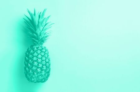 Creative layout. Gold pineapple on mint background with copy space. Top view. Tropical flat lay. Trendy green and turquoise color. Exotic food concept, crazy trend. Banner.