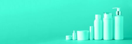 White cosmetic tubes on mint color background with copy space. Skin care, body treatment, beauty concept. Trendy green and turquoise color. Banner.