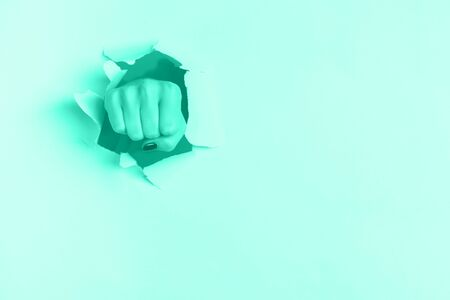 Female fist punching through mint color paper background. War, struggle, conflict, feminist concept. Trendy green and turquoise color. Banner with copy space.