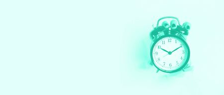 Hand holding black alarm clock through hole in mint color background. Wake up alert concept. Trendy green and turquoise color. Morning routine. Banner with copy space.
