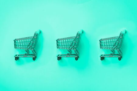 Shopping cart on mint color background. Minimalism style. Creative design. Shop trolley at supermarket. Trendy green and turquoise color. Sale, discount, shopaholism concept Reklamní fotografie