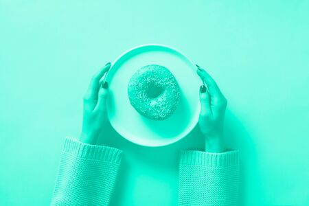 Female hands holding donut on plate over mint color background. Trendy green and turquoise color. Top view, flat lay. Sweet, dessert, diet concept. Weight lost after holidays.