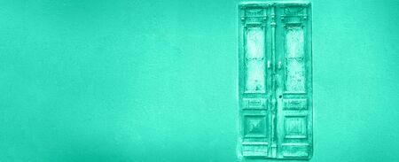 Old wooden and metal door in mint color background. Biscay Green color of the year 2020