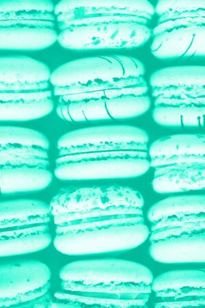 Colorful french macaroons flat lay. Pastel colors macarons on mint color background. Trendy green and turquoise color. Holidays and celebrations concept. Sweet gift for woman, girl. Banner. Banco de Imagens