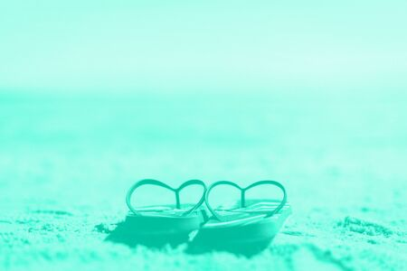 Summer slippers. Flip flop on sand beach background in mint color. Copy space, top view. Trendy green and turquoise color. Holiday, vacation and travel concept. Banner.